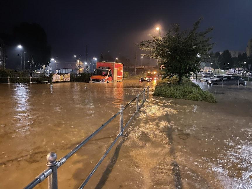 Autos und ein Rettungswagen sind auf einer überfluteten Straße zu sehen.