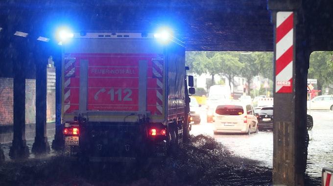 Ein Feuerwehr-Fahrzeug fährt durch eine durchflutete Überführung.