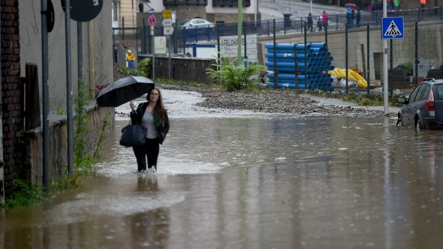 Unwetter in NRW. Eine Frau läuft mit Regenschirm durch eine überflutete Straße in Hagen.