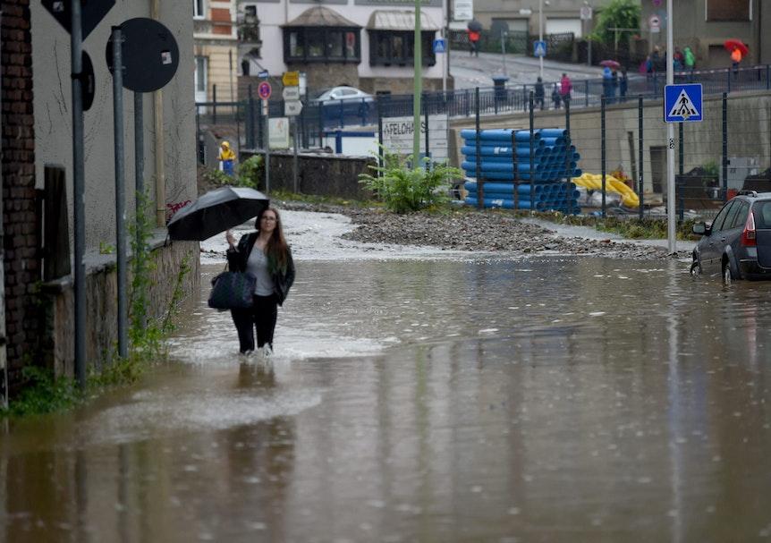 Eine Frau mit einem Regenschirm läuft am 14. Juli 2021 über eine überschwemmte Straße in Hagen.