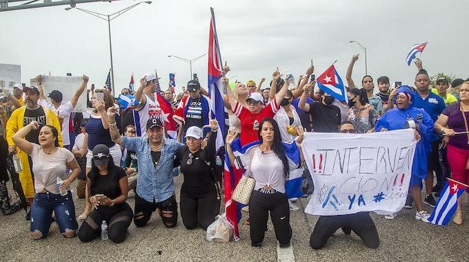 Mehrere Menschen versammeln sich in Miami (USA) mit Fahnen von Kuba und Postern auf dem Palmetto Expressway am Coral Way zur Unterstützung der Demonstranten in Kuba. Sie sind symbolisch auf die Knie gegangen.