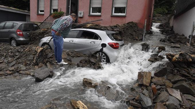 Ein Anwohner schaut sich am Donnerstag (15. Juli) die Schäden in Hagen an, die die Überflutung der Nahma am Vorabend mit sich gebracht hat. Durch die heftigen Regenfälle war das Flüsschen zum reissenden Fluss geworden, ein silbernes Auto steht inmitten des Stroms und dem vielen Geröll, das er mit sich gerissen hat.