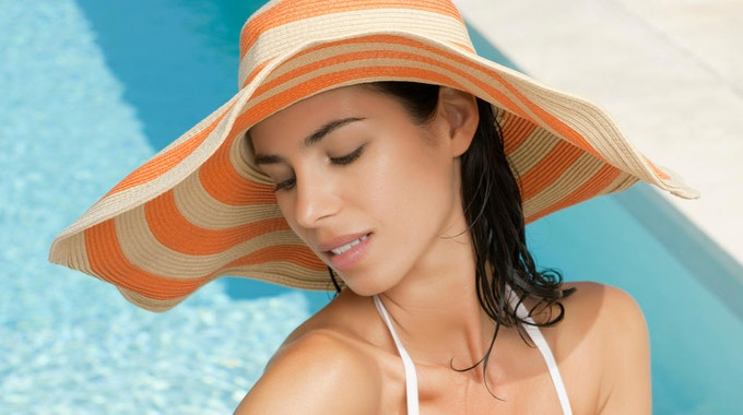 Eine Frau sitzt am Pool und cremet sich den Arm mit Sonnencreme ein.