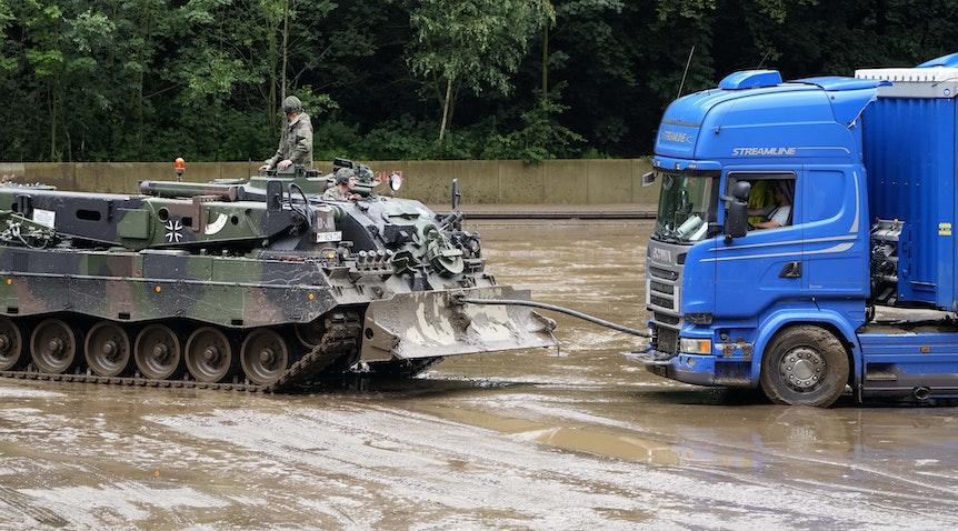 Ein Panzer der Bundeswehr zieht am Donnerstag (15. Juli) einen Lkw in Hagen aus dem Schlamm, nachdem es dort zu Überschwemmungen kam. Die Bundeswehr unterstützt die Hilfs- und Aufräumarbeiten in der Region.