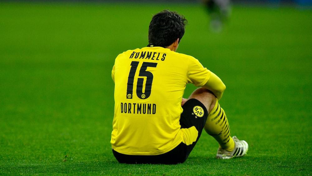Mats Hummels sitzt auf dem Rasen mit den Armen auf den Knien gestützt
