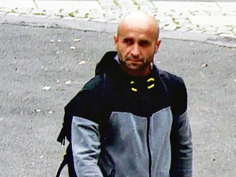 Ein Mann mit Glatze geht über einen asphaltierten Platz.