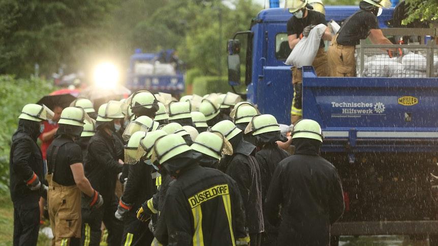 14.07.2021, Nordrhein-Westfalen, Düsseldorf: Feuerwehrleute arbeiten in der Ostparksiedlung. Die Feuerwehr versucht, die Wassermassen mit Sandsäcke zu stoppen. Foto: David Young/dpa +++ dpa-Bildfunk +++