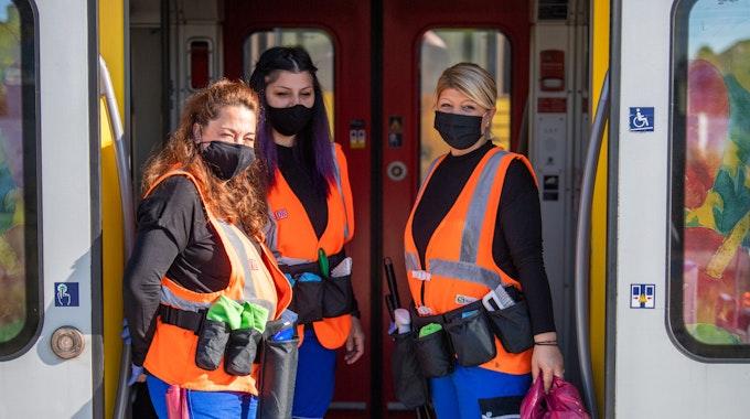 Drei Reinigungskräfte der mobilen Reinigung der S-Bahn München stehen in der Tür einer stehenden S-Bahn und sorgen dafür, dass während der Corona-Zeit Kontaktflächen richtig desinfiziert sind.