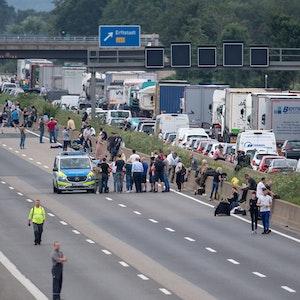 Autofahrer und Lastwagen stehen auf der Autobahn 1 im Stau. Das Regen-Unwetter in Nordrhein-Westfalen hat auf zahlreichen Autobahnen für überflutete Fahrbahnen gesorgt.