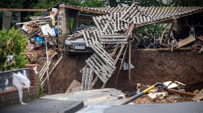 Ein Auto hängt im Ortsteil Blessem über einem Abgrund. Starkregen hatte am Mittwoch (14. Juli 2021) zu schweren Überschwemmungen und Hochwasser geführt.