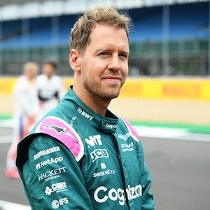Sebastian Vettel lächelt auf der Rennstrecke der Formel 1 in Silverstone in die Kamera.