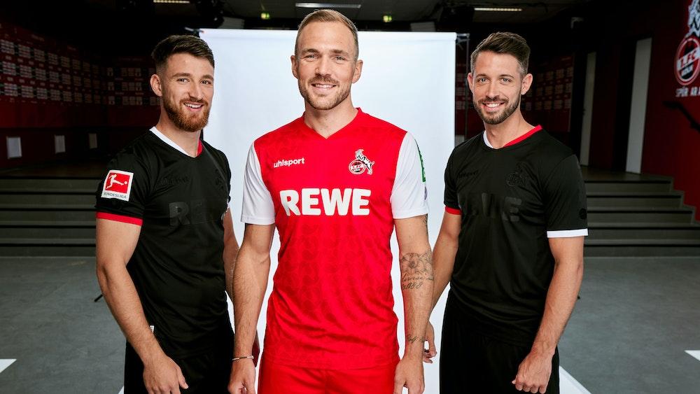 Die Profis Rafael Czichos (M.) sowie Salih Özcan (l.) und Mark Uth präsentieren das neue Auswärtstrikot in Rot und Weiß sowie das schwarze Ausweichdress des 1. FC Köln.