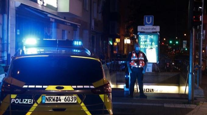 Ein Streifenwagen und ein Beamter stehen am Abgang zur U-Bahnhaltestelle Piusstraße.