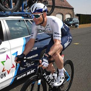 André Greipel fährt neben dem Teamwagen vom Team Israel Start-Up Nation auf seinem Rad.