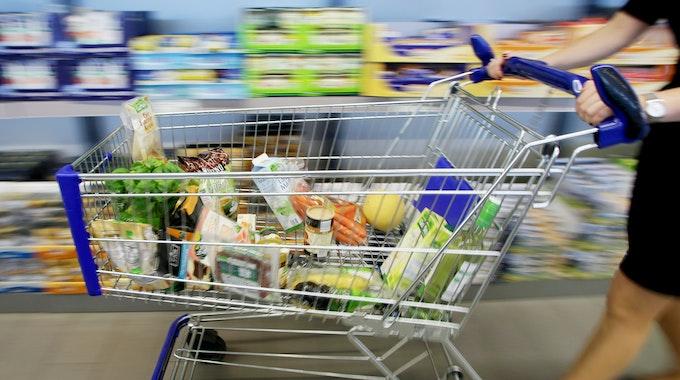Kundin fährt gefüllten Einkaufswagen durch Aldi-Filiale.
