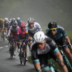Bei der Tour de France fährt das Peloton im Nebel eine Bergabfahrt hinunter.