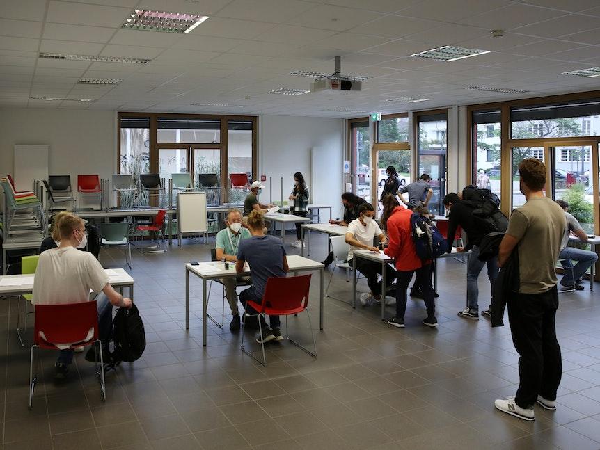 Studierende der Uni Köln warten in einem Raum auf ihre Impfung.