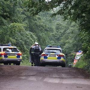 Polizeifahrzeuge stehen auf einer Straße, um die Zufahrt zum Unglücksort zu sperren.