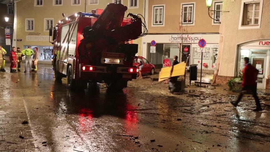 Unwetter Österreich: Nächtliche Aufräumarbeiten auf einer vom Hochwasser betroffenen Straße in der Altstadt von Hallein bei Salzburg.