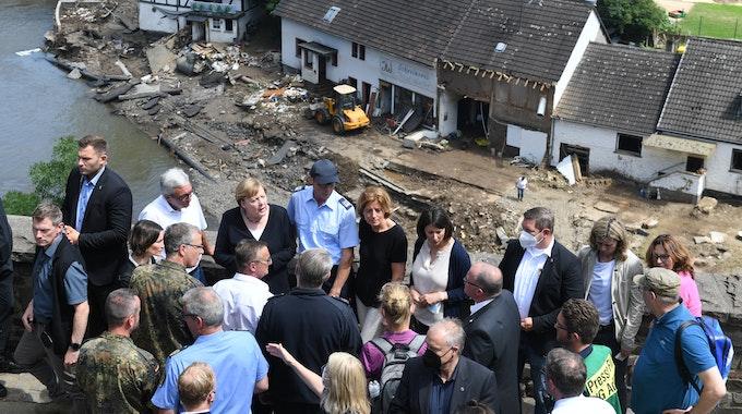 Bundeskanzlerin Angela Merkel (3.v.l.) und die rheinland-pfälzische Ministerpräsidentin Malu Dreyer (5.v.l.,SPD) stehen während ihres Besuchs in den vom Hochwasser betroffenen Gebieten auf einer Brücke.