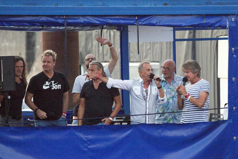 Die Bläck Fööss winken auf einer Bühne ihren Fans zu.