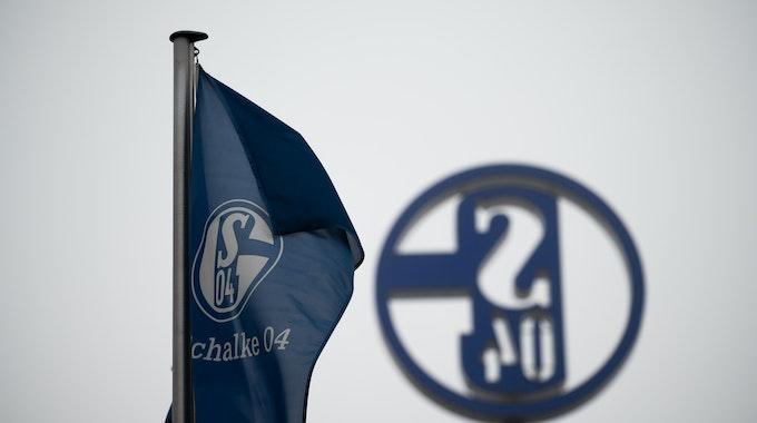 Eine Fahne mit dem Logo des FC Schalke 04 weht vor grauem Himmel.