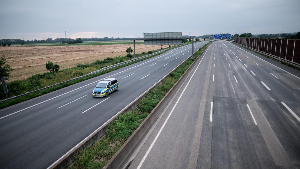 Die gesperrte Autobahn A1 am 16. Juli 2021 bei Blessem in Erftstadt. Ein Polizeiwagen kontrolliert die Strecke.