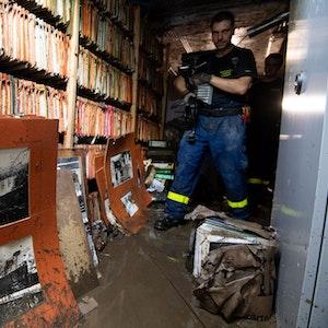 Ein Helfer des Technischen Hilfswerks (THW) läuft durch das überflutete Stadtarchiv.