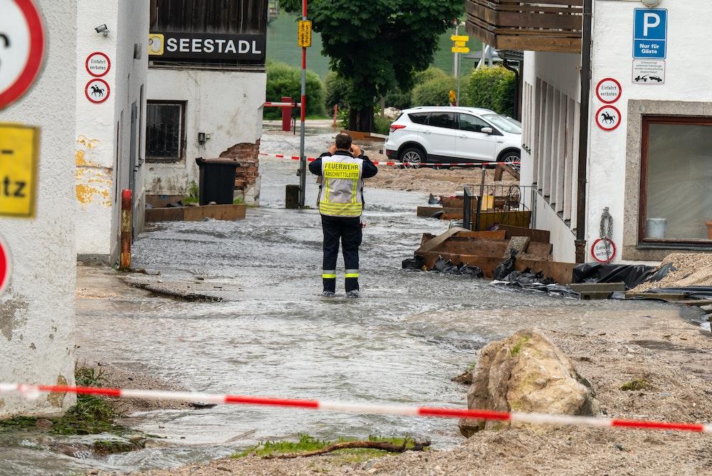 Ein Feuerwehrmann steht auf einer Straße, die zum Königssee führt, und über die noch Wasser abfließt.