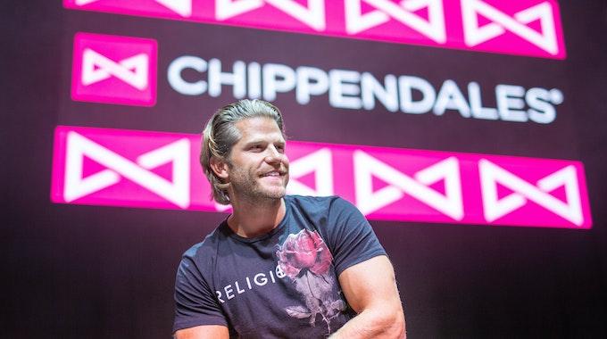 Paul Janke gibt es jetzt auf Onlyfans. Hier sitzt er in München vor dem Logo der Strippercombo Chippendales.