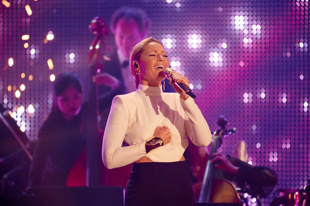 Helene Fischer singt beim RTL-Jahresrückblick mit Mikrofon in der Hand und ihrer Band im Hintergrund.