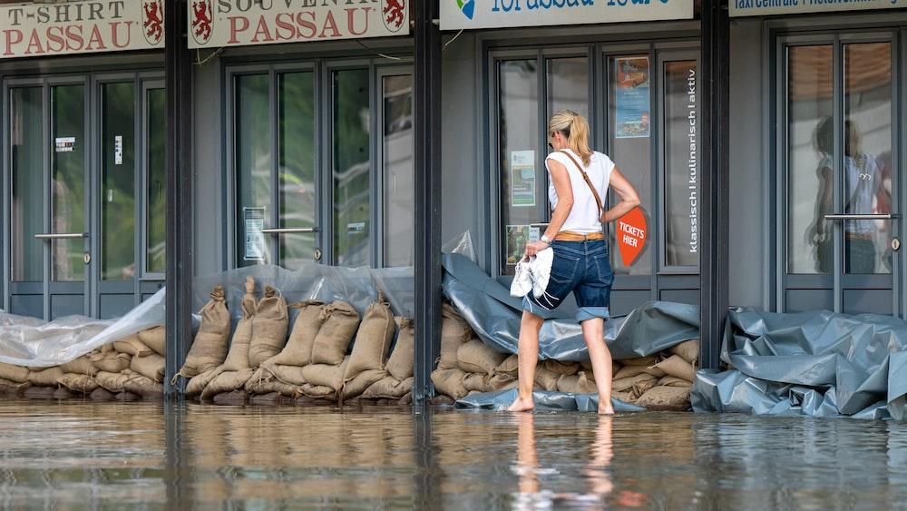 Eine Frau geht in Passau an der Uferpromenade an einem Reise-Center vorbei, das mit Sandsäcke vor den Türen vor dem Wasser der Donau abgedichtet wurde.