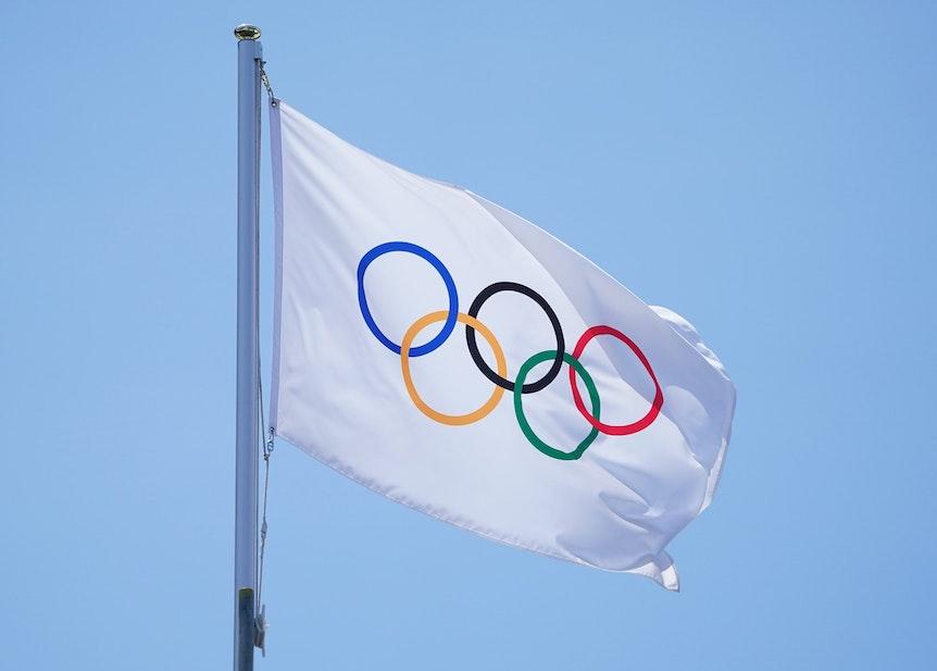 Die olmpische Fahne mit den olympischen Ringen weht in Tokio an einem Fahnenmast.