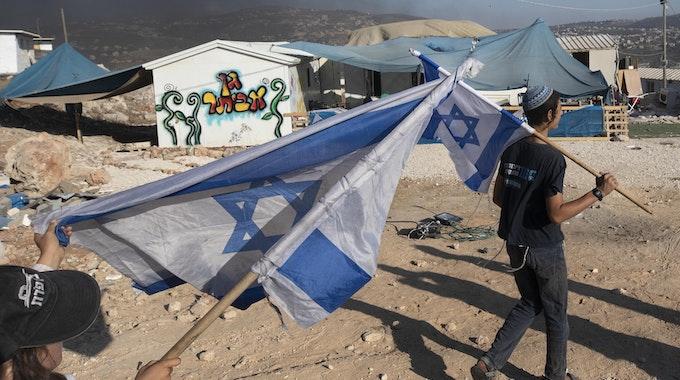 Zwei Menschen schwenken in einer Siedlung Israel-Flaggen im Westjordanland.