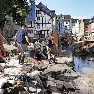 Helfer gehen durch den Ortskern. In Bad Münstereifel hat die über die Ufer getretene Erft erhebliche Schäden angerichtet.