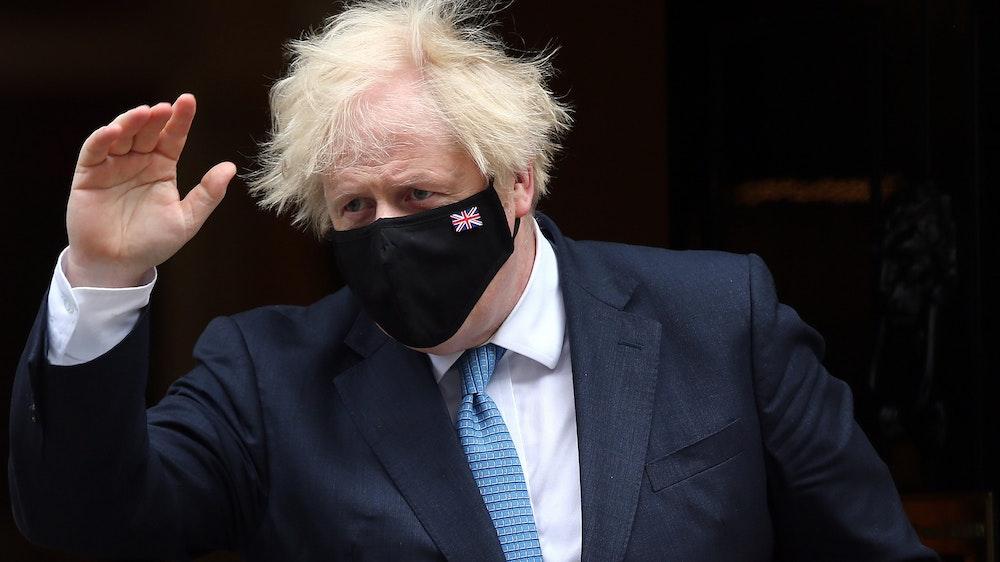 Großbritanniens Premier Minister Boris Johnson trägt eine dunkle Maske und winkt mit der rechten Hand.