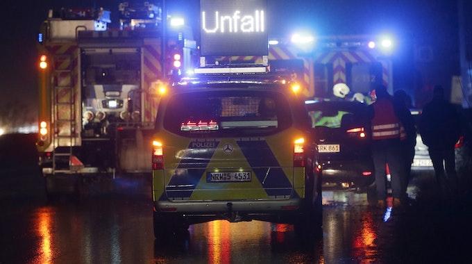 Polizei- und Feuerwehrfahrzeuge mit Blaulicht sichern eine Unfallstelle auf der Autobahn 3.