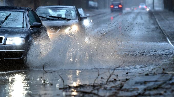 Gelsenkirchen: Autos fahren langsam durch eine tiefe Pfütze die sich durch Starkregen auf einer Straße gebildet hat.