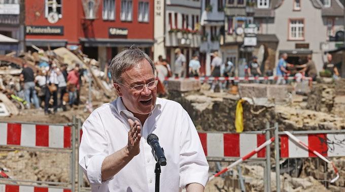 Armin Laschet spricht in ein Mikrofon. Im Hintergrund sieht man die Unwetterschäden in Bad Münstereifel, die mit einem Bauzaun abgesperrt sind.