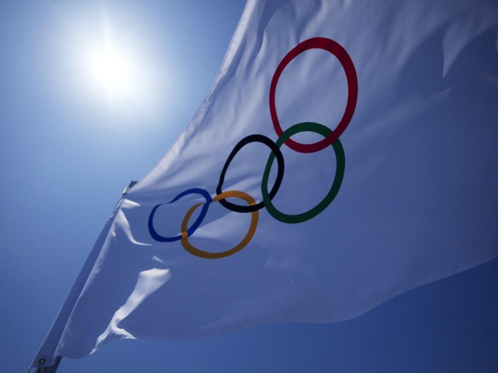 Die olympische Flagge mit den olympischen Ringen flattert im Wind vor blauem Himmel.