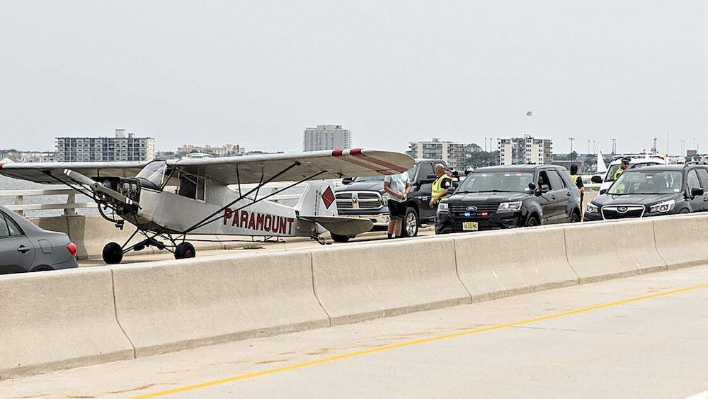 Rettungskräfte sprechen mit Landon Lucas (18) einem Piloten, der für Paramount Air Service fliegt, nachdem er auf einer Autobahnbrücke in Ocean City notgelandet ist.