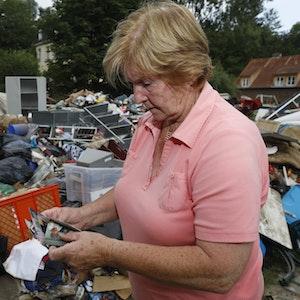 Frau in Köln vor Müllberg nach Hochwasser.