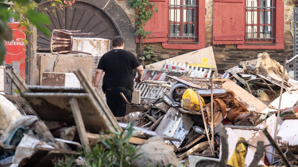Am 18. Juli 2021 läuft ein Anwohner durch die Trümmer-Berge in der Stadt Ahrweiler.