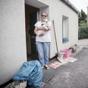 Eine Frau steht mit ihrem Hund vor ihrem Haus, das beim Hochwasser in Düsseldorf beschädigt wurde.