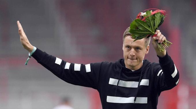 Felix Kroos mit einem Blumenstrauß in der Hand
