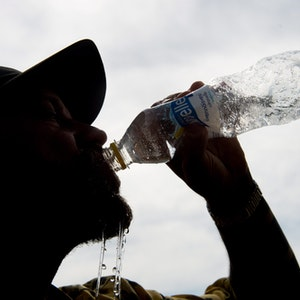 Auf unseren Symbolfoto ist ein Mann mit Mütze zu sehen, der aus einer Flasche Wasser trinkt.