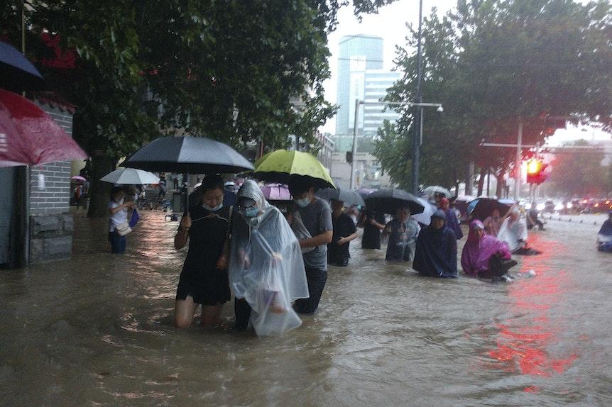 Menschen waten in der zentralchinesischen Provinz Henan durch eine überflutete Straße.