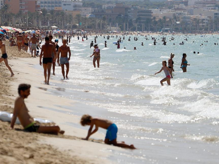 Menschen sonnen sich und schwimmen am Strand von Arenal auf Mallorca.
