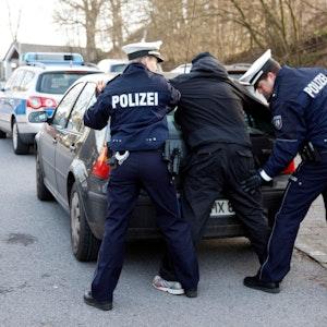 Polizisten kontrollieren eine Person am Heck ihres Pkw.