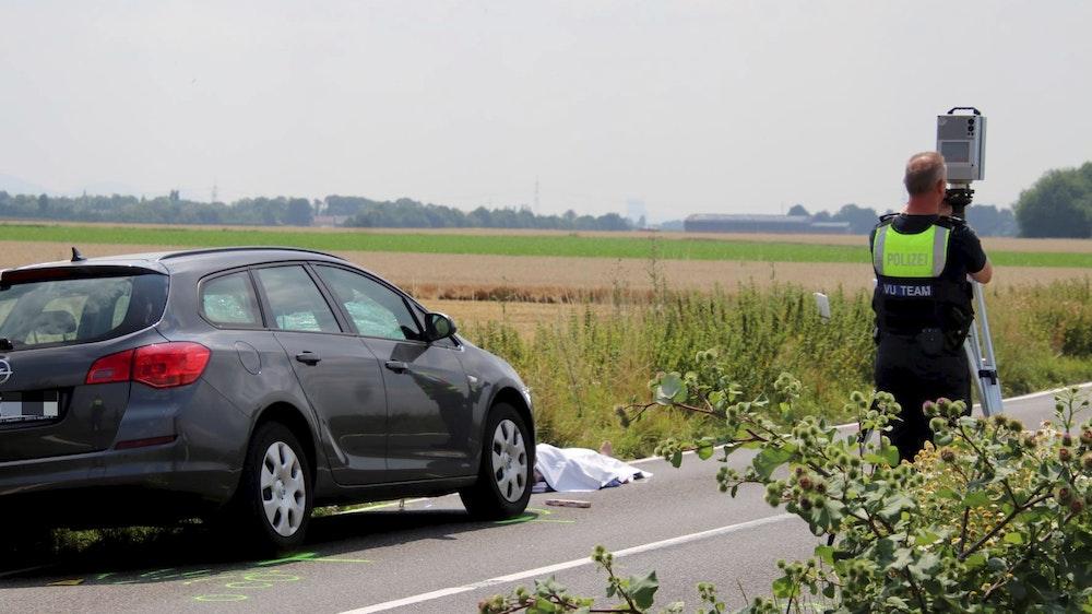 Ein Auto steht auf der Fahrbahn, davor liegt ein abgedeckter Körper.